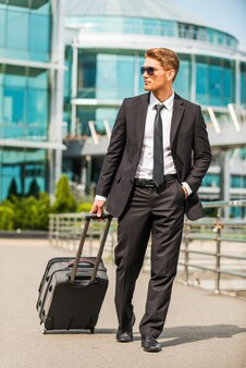 이동 중에 사업가입니다. 야외에서 걷는 동안 가방을 들고 정장을 입은 자신감 있는 젊은 사업가