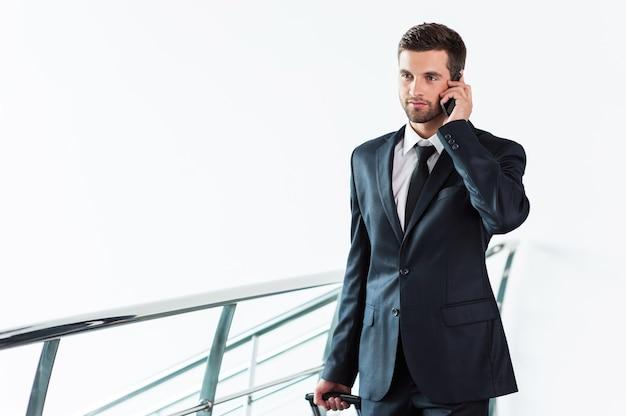 이동 중인 사업가입니다. 양복을 입은 자신감 있는 젊은 사업가가 휴대전화로 통화하고 여행가방을 들고 걸어가는 동안