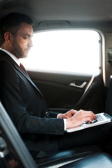 이동 중에 사업가입니다. 차 안에 앉아 노트북 작업을 하는 자신감 있는 젊은 사업가
