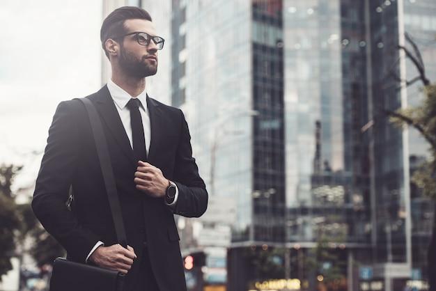 外出先でのビジネスマン。フルスーツで自信を持って若くてハンサムな男のローアングルビュー