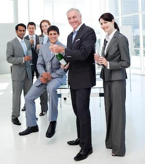 成功を祝うためにシャンパンのボトルを開くビジネスマン