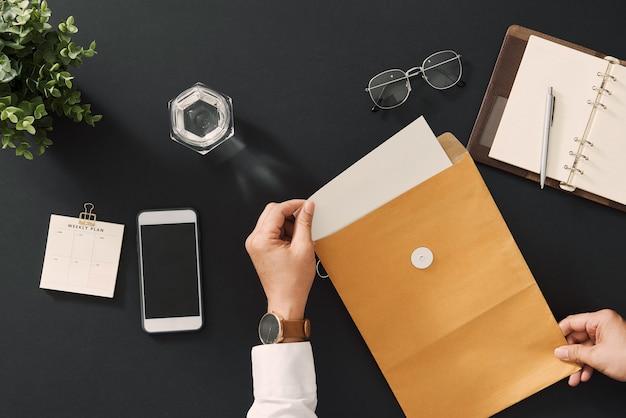 Бизнесмен, открытие бизнес-отчета в конверте письма - бизнес-концепция