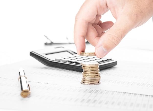Бизнесмен или бухгалтер, подсчитывающий деньги и делая стопку монет на финансовых данных. финансирование, бухгалтерский учет и банковское понятие.