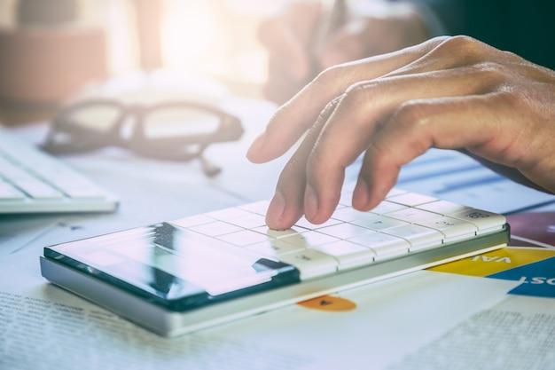 사업 또는 회계사 비즈니스 데이터 개념을 계산하기 위해 계산기 작업.