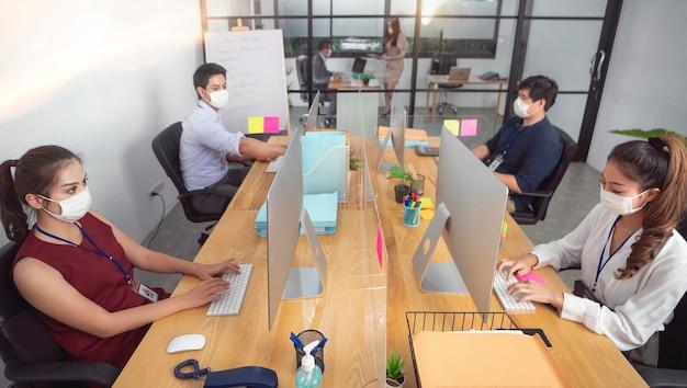 사업가 또는 회사원이 covid-19 또는 코로나 바이러스 질병을 보호하기 위해 일하고 마스크를 착용하고 있지만 비즈니스는 지속적이어야합니다.