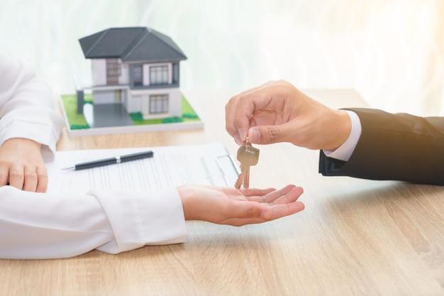 女性に家の鍵を与えるビジネスマンまたはセール男