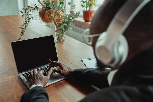 Бизнесмен или студент, работающий из дома, изолированы или находятся на карантине из-за коронавируса. афро-американский мужчина с помощью ноутбука, планшета и наушников. онлайн конференция, урок, удаленный офис.