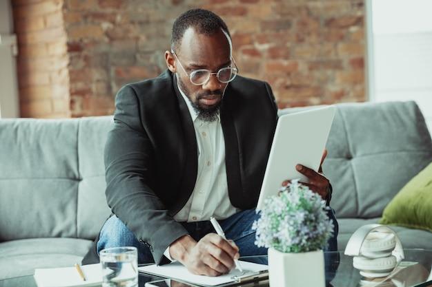 집에서 일하는 사업가나 학생은 코로나바이러스 때문에 격리되거나 격리를 유지합니다. 노트북, 태블릿, 헤드폰을 사용하는 아프리카계 미국인 남자. 온라인 회의, 수업, 원격 사무실.