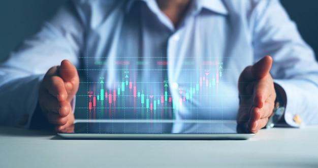 Бизнесмен или трейдер показывает на планшете растущую виртуальную голографию