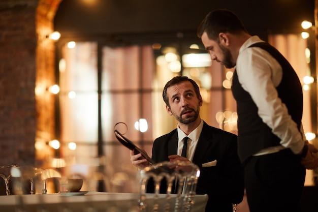 Бизнесмен заказывает ужин в ресторане