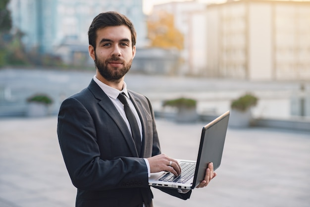 Businessman outdoors on a background of cityscapes holding a laptop looking straight.