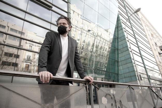 Бизнесмен на открытом воздухе перед современным зданием