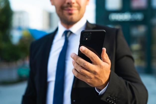 Бизнесмен на открытом воздухе, глядя на свой телефон