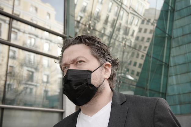 Бизнесмен на открытом воздухе в черной маске для предотвращения заражения коронавирусом