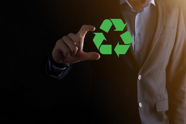 어두운 배경 위에 사업가가 재활용 아이콘을 들고 손에 서명합니다. 생태학, 환경