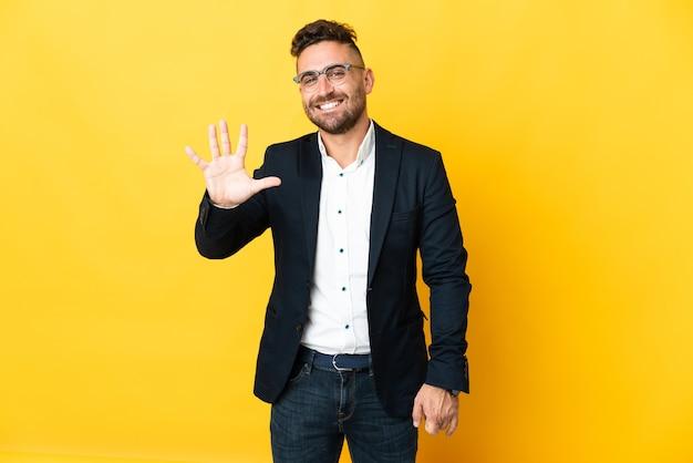 Бизнесмен на изолированном желтом фоне, считая пять пальцами