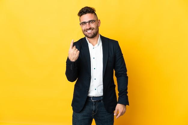 Бизнесмен на изолированном желтом фоне, делая приближающийся жест