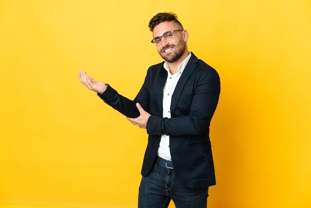 孤立した黄色の背景の上のビジネスマンは、来て招待するために手を横に伸ばします