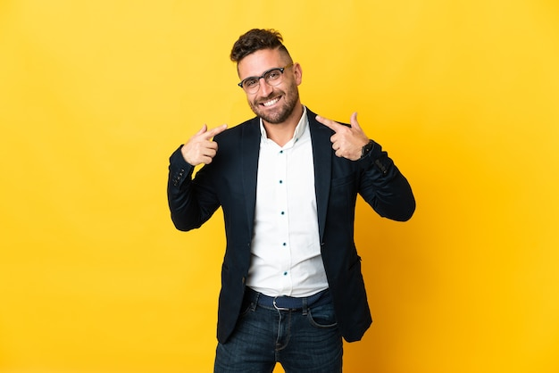 Бизнесмен на изолированном желтом фоне, показывая жест