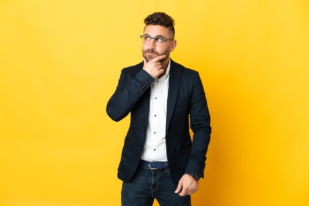 Бизнесмен на изолированном желтом фоне с сомнениями и мышлением