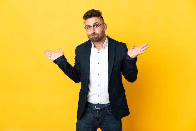 Бизнесмен на изолированном желтом фоне, сомневаясь, поднимая руки