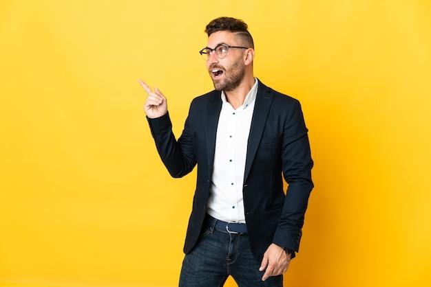 Бизнесмен на изолированном желтом фоне, намереваясь реализовать решение, подняв палец вверх