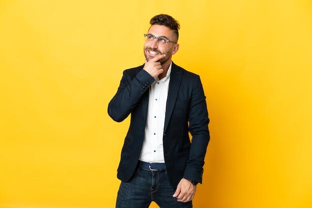 Бизнесмен на изолированном желтом фоне, глядя вверх, улыбаясь