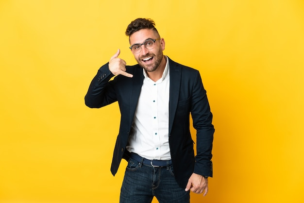 Бизнесмен на изолированном желтом фоне, делая телефонный жест. перезвони мне знак