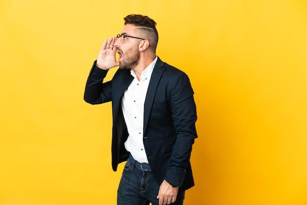 Бизнесмен на изолированном желтом фоне кричит с широко открытым ртом в сторону