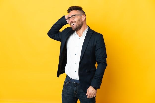 Бизнесмен на изолированном желтом фоне много улыбается