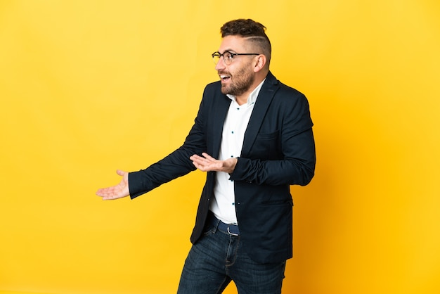 Бизнесмен на изолированном желтом фоне с удивленным выражением лица, глядя в сторону