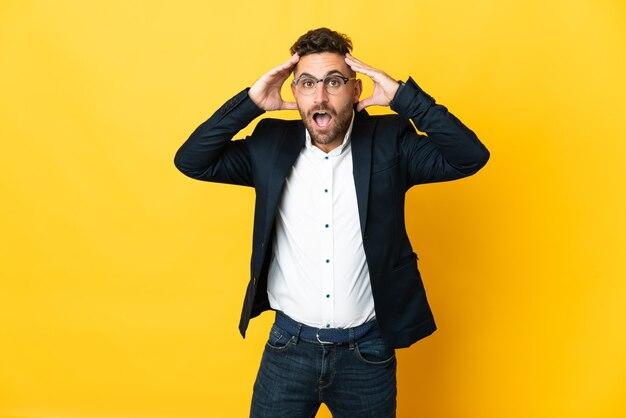 Бизнесмен на изолированном желтом фоне с выражением удивления