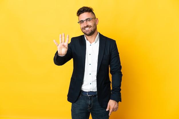 Бизнесмен над изолированным желтым счастливым и считая четыре пальцами