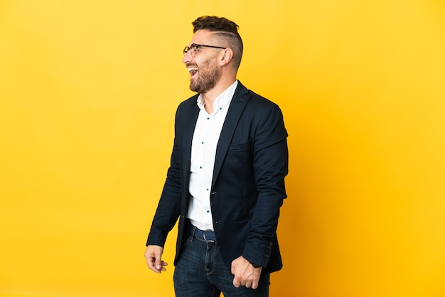 Бизнесмен над изолированной желтой стеной смеется в боковом положении