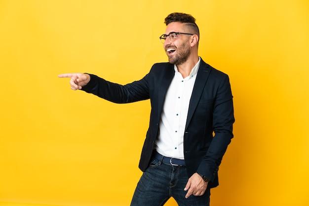 Бизнесмен над изолированной желтой стеной, указывая пальцем в сторону и представляя продукт