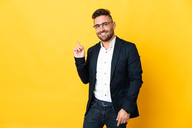 Бизнесмен над изолированной желтой стеной, указывая пальцем в сторону