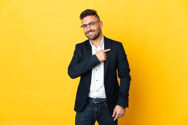 Бизнесмен над изолированной желтой стеной, указывая в сторону, чтобы представить продукт
