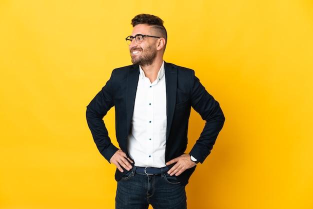 Бизнесмен над изолированной желтой стеной позирует с руками на бедрах и улыбается