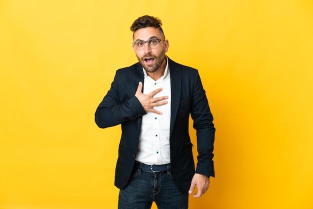 Бизнесмен над изолированной желтой стеной удивлен и шокирован, глядя вправо