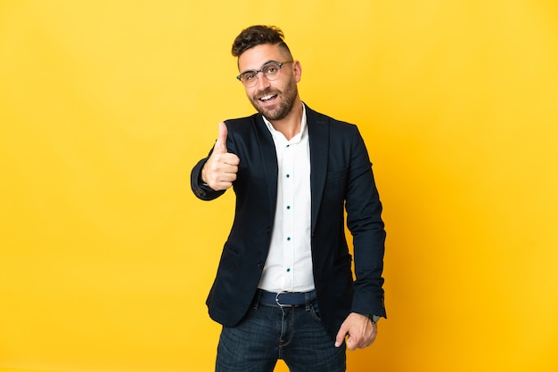 Бизнесмен над изолированной желтой стеной с большими пальцами руки вверх, потому что произошло что-то хорошее