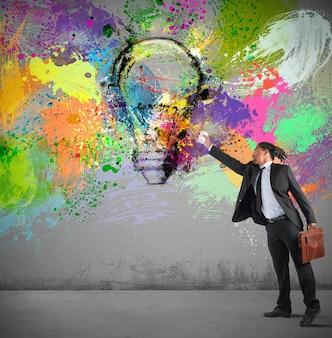 사업가 벽에 스프레이와 화려한 아이디어 페인트