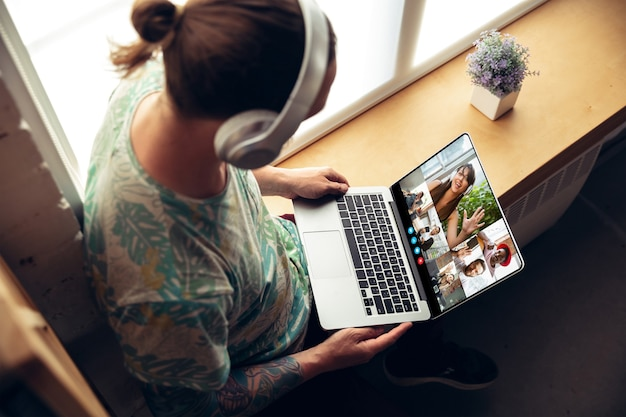 ビジネスマンは、仮想会議中にノートパソコンの画面を見ているビデオ会議に参加し、ビジネス用のビデオ通話ウェブカメラアプリをクローズアップします。在宅勤務、フリーランス、教育、ライフスタイルのコンセプト。