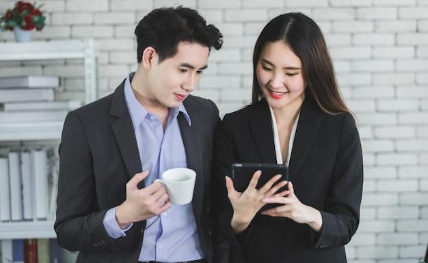 Бизнесмен партнеры, работая вместе с планшетом и бизнесменом, держащим чашку