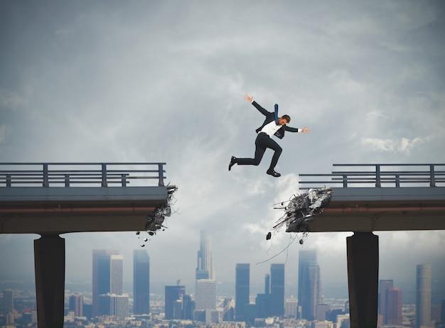 ビジネスマンは大きなジャンプで壊れた橋を通過します