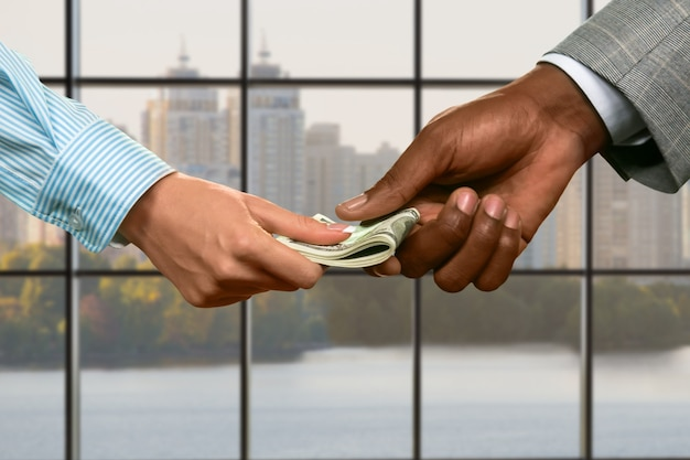 Businessman passes cash to woman. money transfer on daytime background. take what belongs to you. fair price in deed.