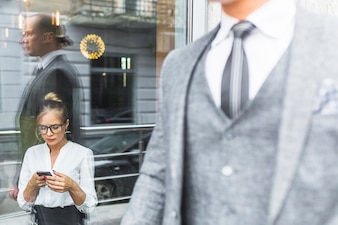 Businessman passing by woman using mobile phone