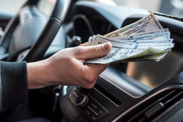 사업가는 제품이나 서비스에 대해 지불하고 차에 앉아있는 동안 달러를 제공합니다. 금융 개념