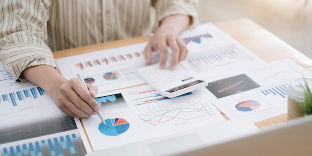 Businessman pen pointing turnover with graph chart report and use calculato for analysis data
