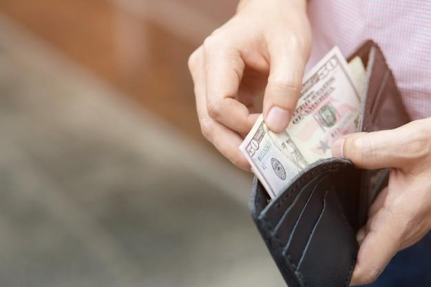 Бизнесмен человек, держащий бумажник в руках человека, берет деньги из кармана.