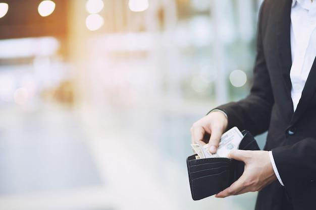 사업가 사람의 손에 지갑을 들고 주머니에서 돈을.